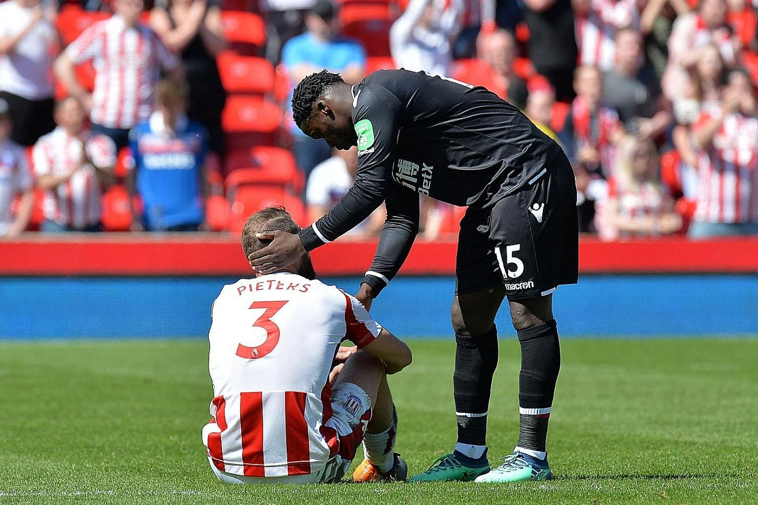 Crestfallen Stoke defender Erik Pieters is comforted by Crystal Palace's Jeffrey Schlupp after the visitors won 2-1 to relegate Stoke from the English Premier League.