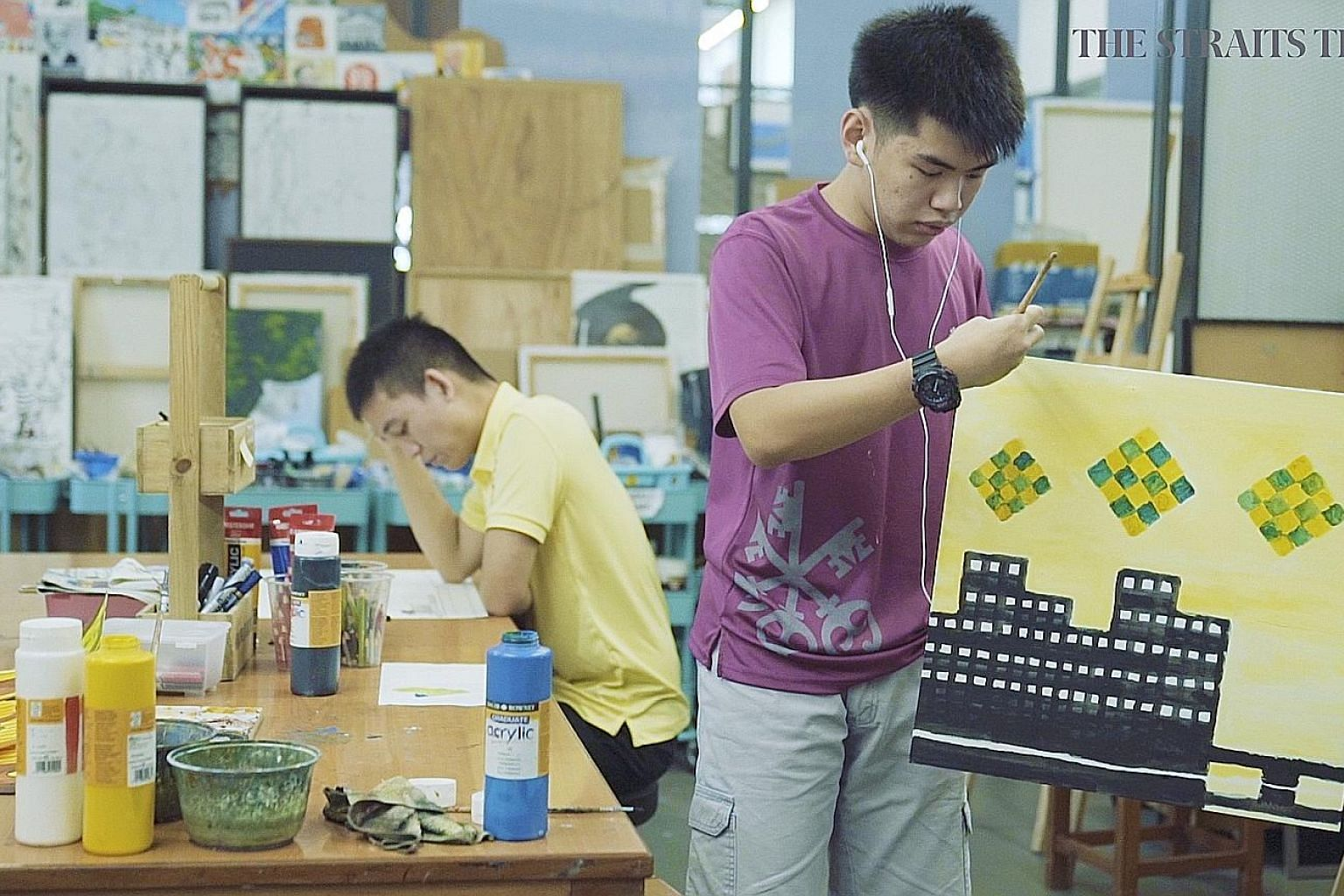 Artists Ezra Chan (far right) and Glenn Phua at work at Pathlight School last month. The two young men with autism, featured in the first episode of the second season of Heroes Among Us, have won acclaim with their artworks.