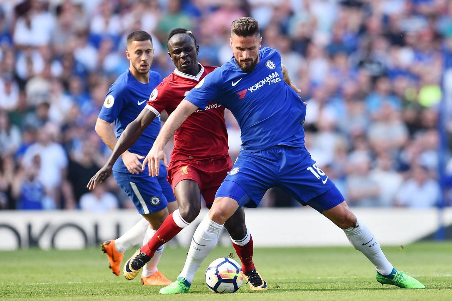 Chelsea striker Olivier Giroud fending off Liverpool forward Sadio Mane, with Eden Hazard looking on, during Sunday's Premier League match that the Blues won 1-0. The Frenchman is the in-form player for Chelsea with five goals in five games.