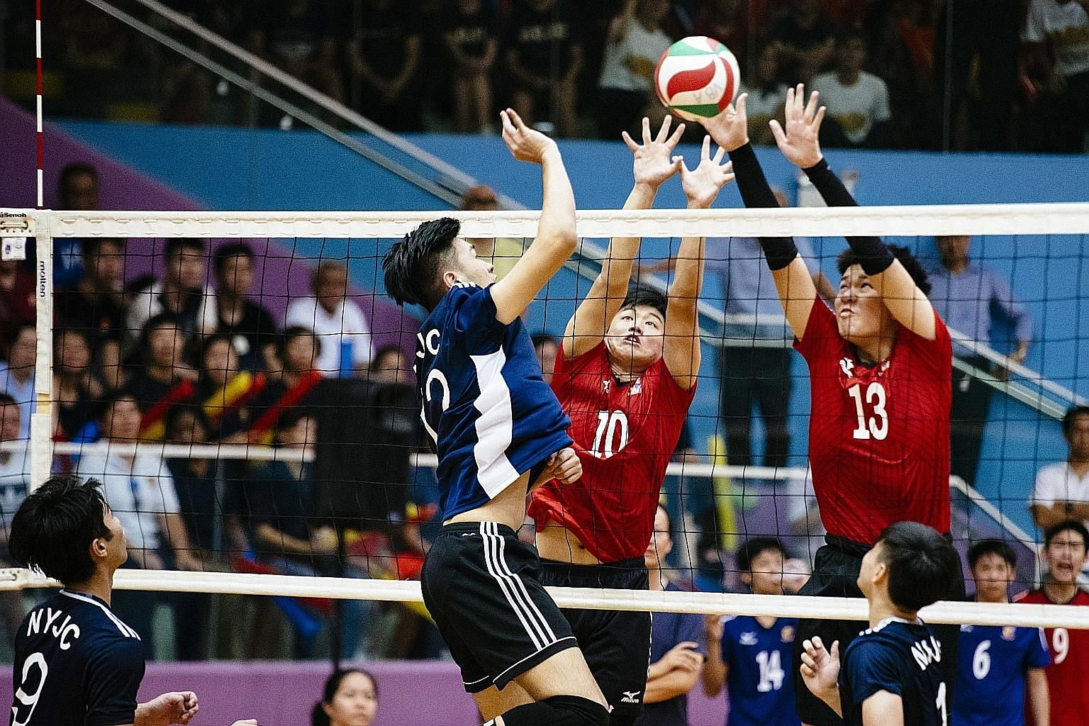 ACJC players Jevvon Tan (middle) and Caleb Seah attempting to block a ball from NYJC's Javier Lee. Nanyang won yesterday's A Division best-of-five final 3-1.