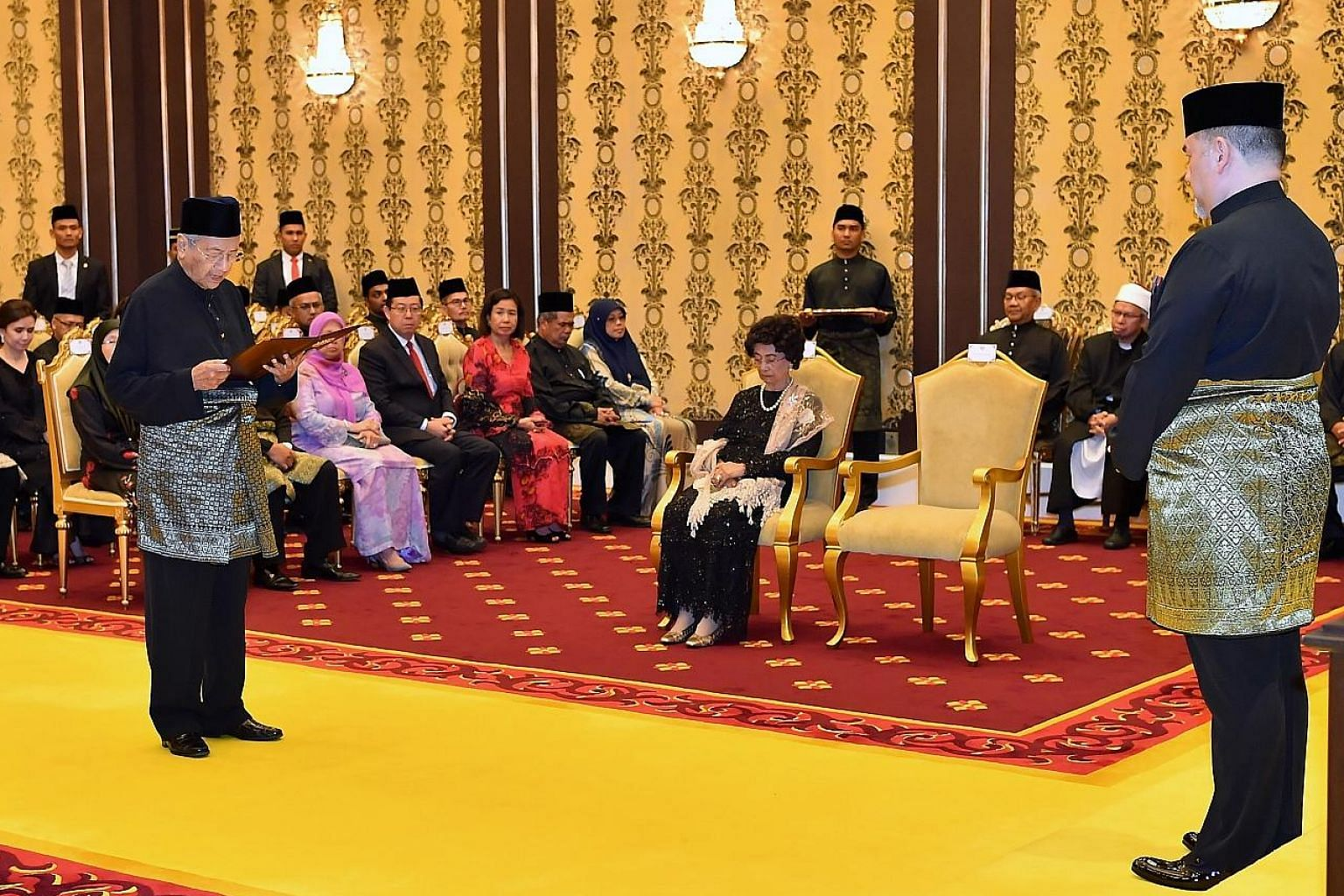 Tun Dr Mahathir Mohamad being sworn in as Prime Minister, witnessed by Sultan Muhammad V, at Istana Negara last night. Dr Mahathir's wife Siti Hasmah Mohd Ali (seated facing him) was among those present. The 92-year-old Pakatan Harapan leader is now