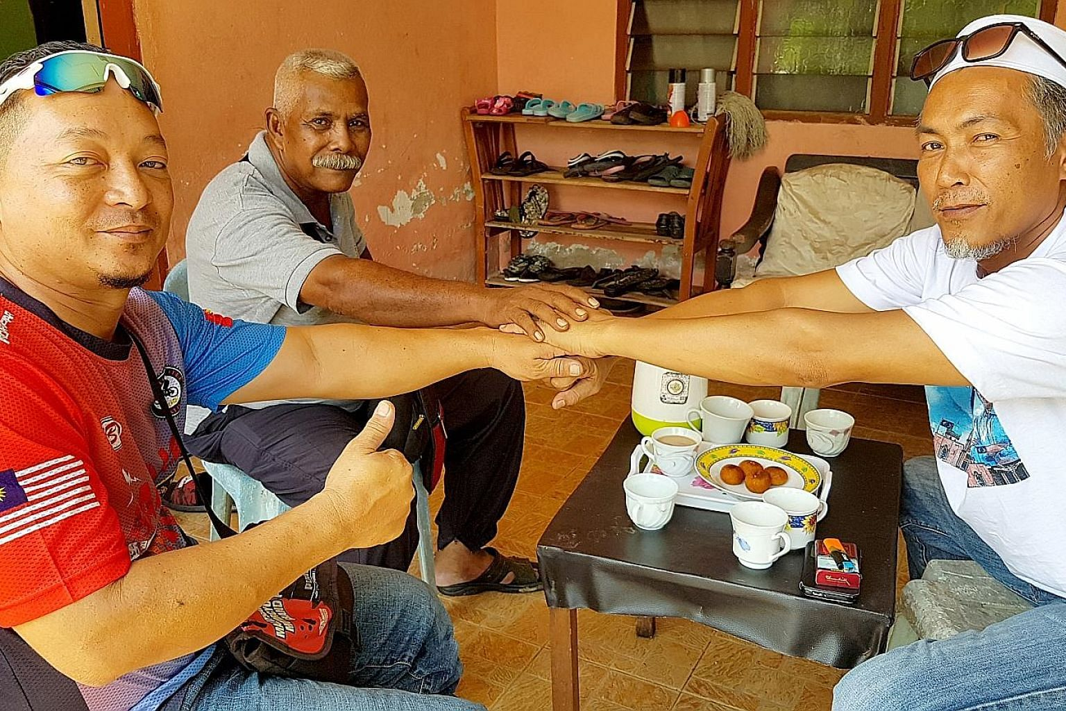 Friends (from far right) Ahmad Tarmizi Din, Bahadun Salim and Effendi Yakob, who all voted for different parties in Wednesday's election, having breakfast together in Kedah yesterday. Supporters of Tun Dr Mahathir Mohamad cheering him outside the She