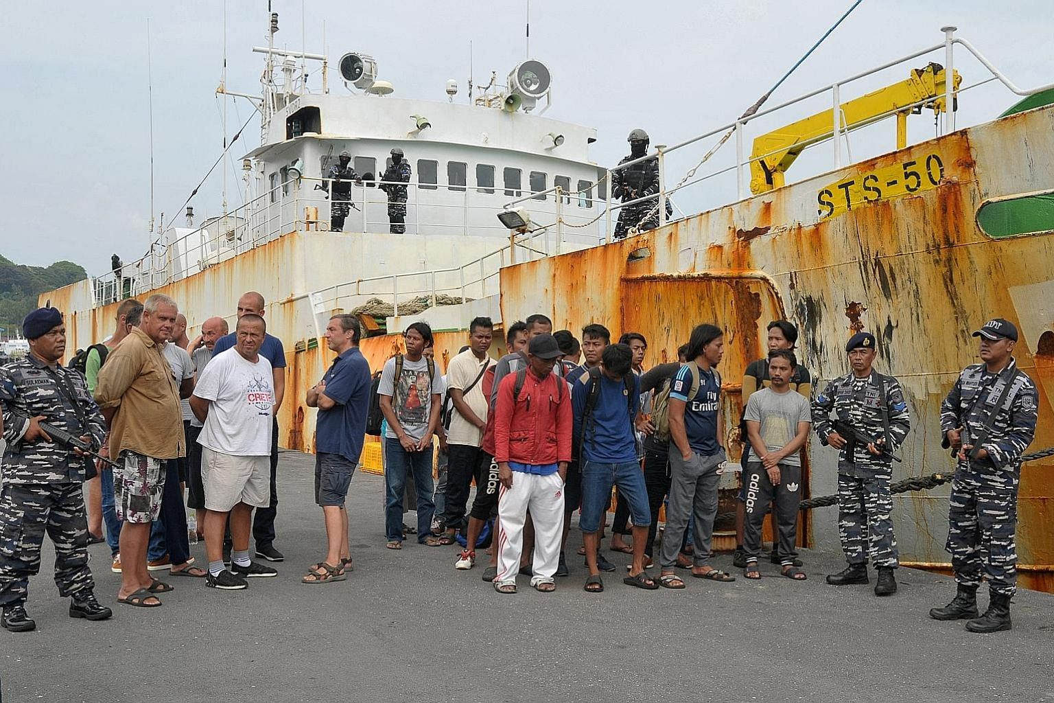 Indonesian navy personnel guarding the detained crew of the stateless STS-50 fishing boat in Sabang, Indonesia, on April 7. Its mostly-Indonesian crew said they had not been paid and that their passports and other documents had been taken away when t