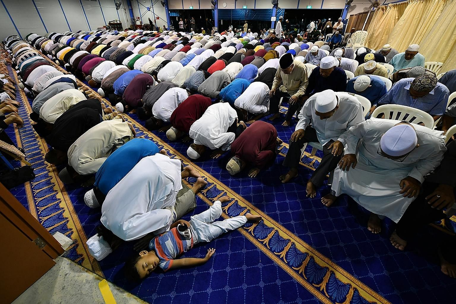 Muslims performing special evening prayers yesterday, the first night of the holy fasting month of Ramadan, at the temporary site of Masjid Darul Ghufran in Tampines. Muslims in Singapore will begin fasting today and celebrate Hari Raya Puasa on June