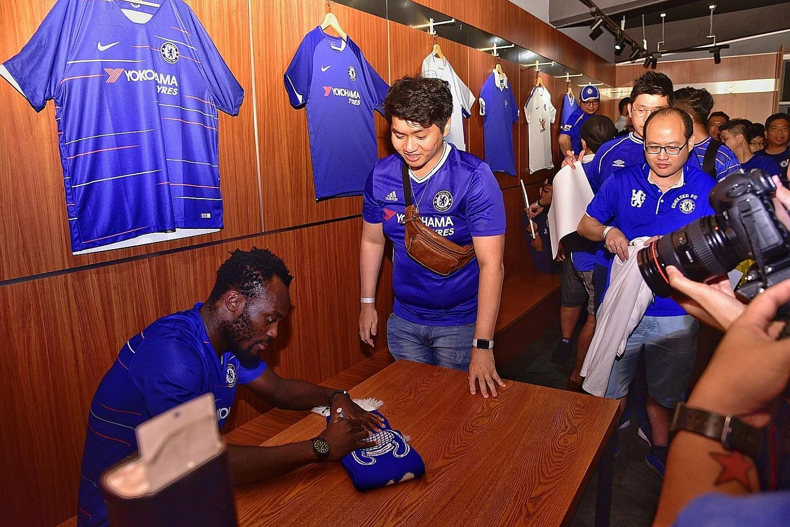 Jonathan Tan, a financial planner, is thrilled to have his Chelsea scarf signed by Michael Essien, who was in town for the club's fan and partner activities on Tuesday.