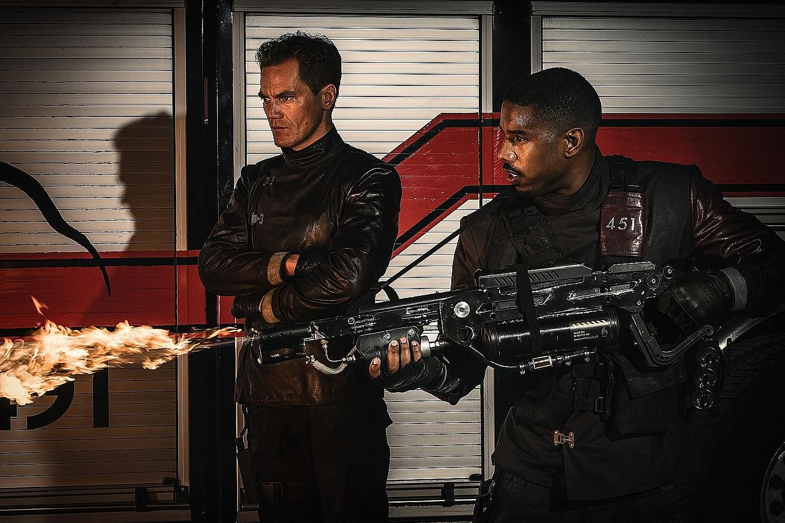Fahrenheit 451's Michael Shannon (left) and Michael B. Jordan are tasked by the government to destroy outlawed written material and alter facts.