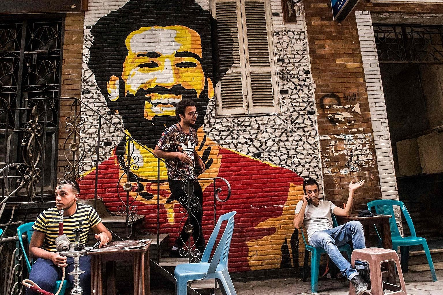 Ahmed Fathy, a 26-year-old Egyptian artist, on the stairs at an open-air cafe in Cairo. He painted the mural depicting the smiling face of Liverpool forward Mohamed Salah.