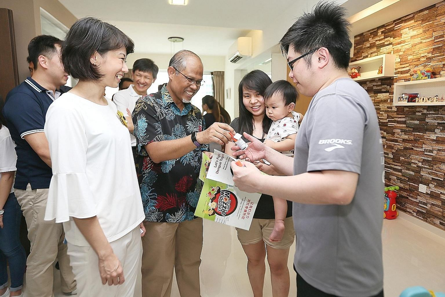 Minister for the Environment and Water Resources Masagos Zulkifli handing out mosquito repellent and pamphlets on the prevention of mosquito breeding yesterday to residents Lim Jun Wei, 33, and Erica Lim, 34, seen here with their one-year-old son Cad