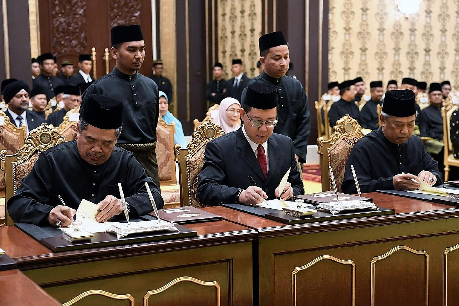 From left: Defence Minister Mohamad Sabu, Finance Minister Lim Guan Eng and Home Minister Muhyiddin Yassin signing their appointment letters at the Istana Negara in Kuala Lumpur yesterday. They were among 13 members of Tun Dr Mahathir Mohamad's core