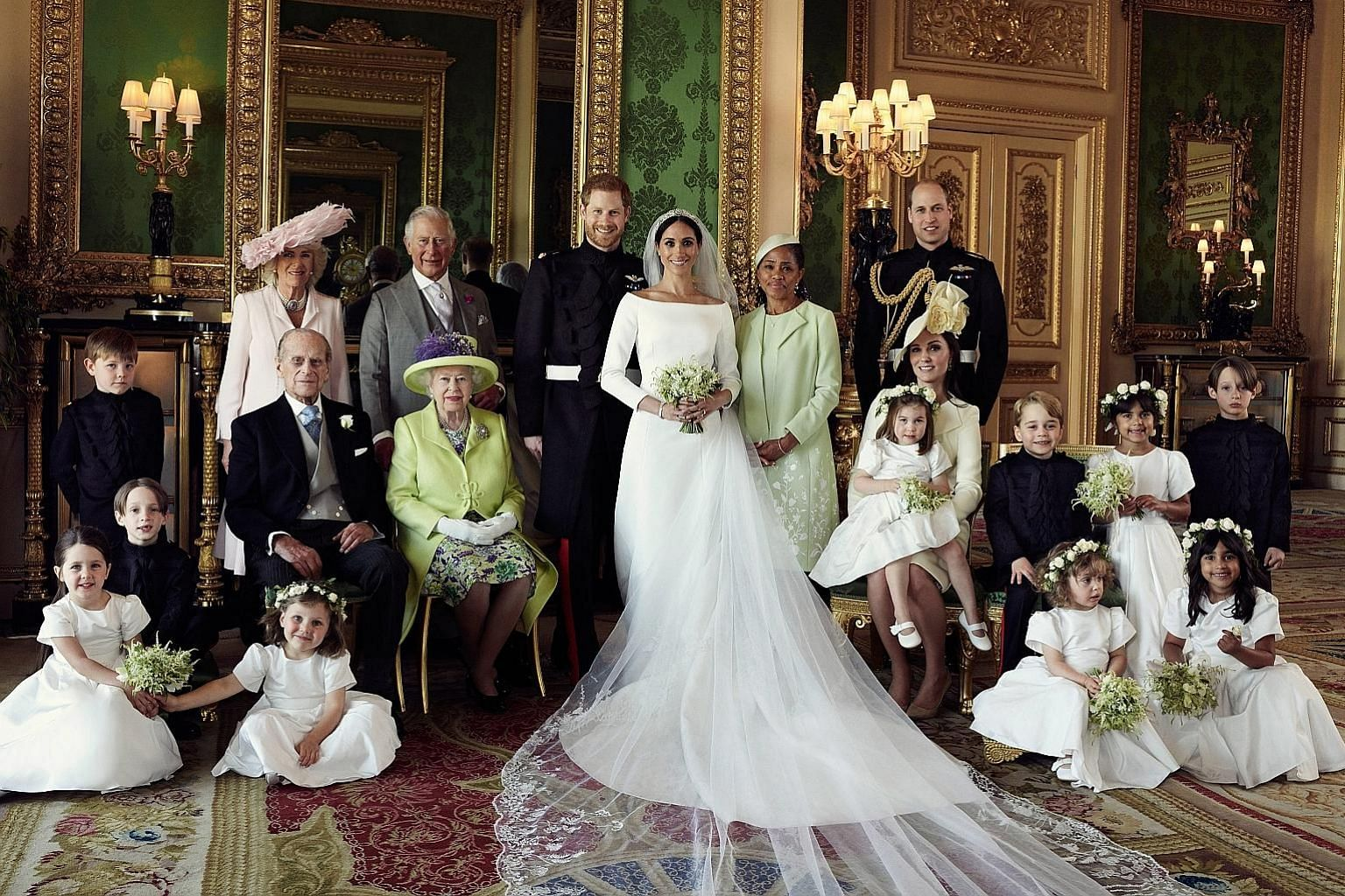 A photo released on Monday by Kensington Palace showing Britain's Prince Harry, the Duke of Sussex (centre), and his new wife Meghan, the Duchess of Sussex, in the Green Drawing Room of Windsor Castle, taken last Saturday. They were joined for the ph