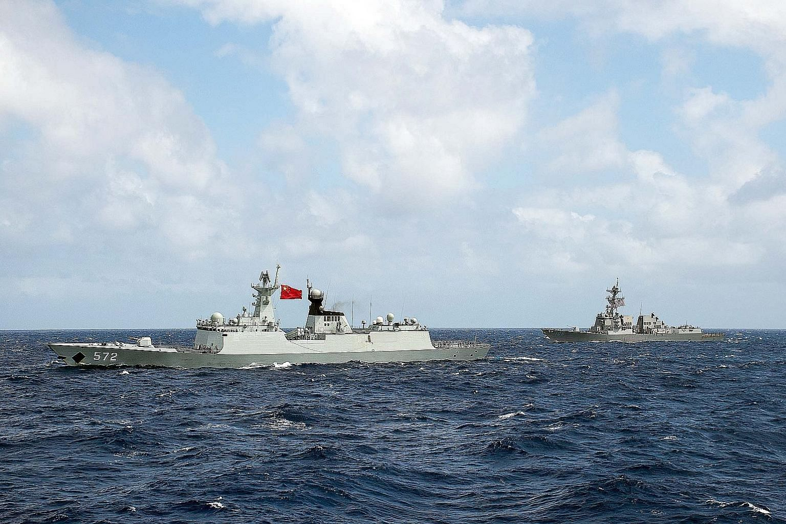 Above: A Chinese frigate and a US guided-missile destroyer at the Rim of the Pacific multilateral maritime war exercise in 2016. Left: Satellite imagery showing what the CSIS Asia Maritime Transparency Initiative calls the deployment of new weapons s