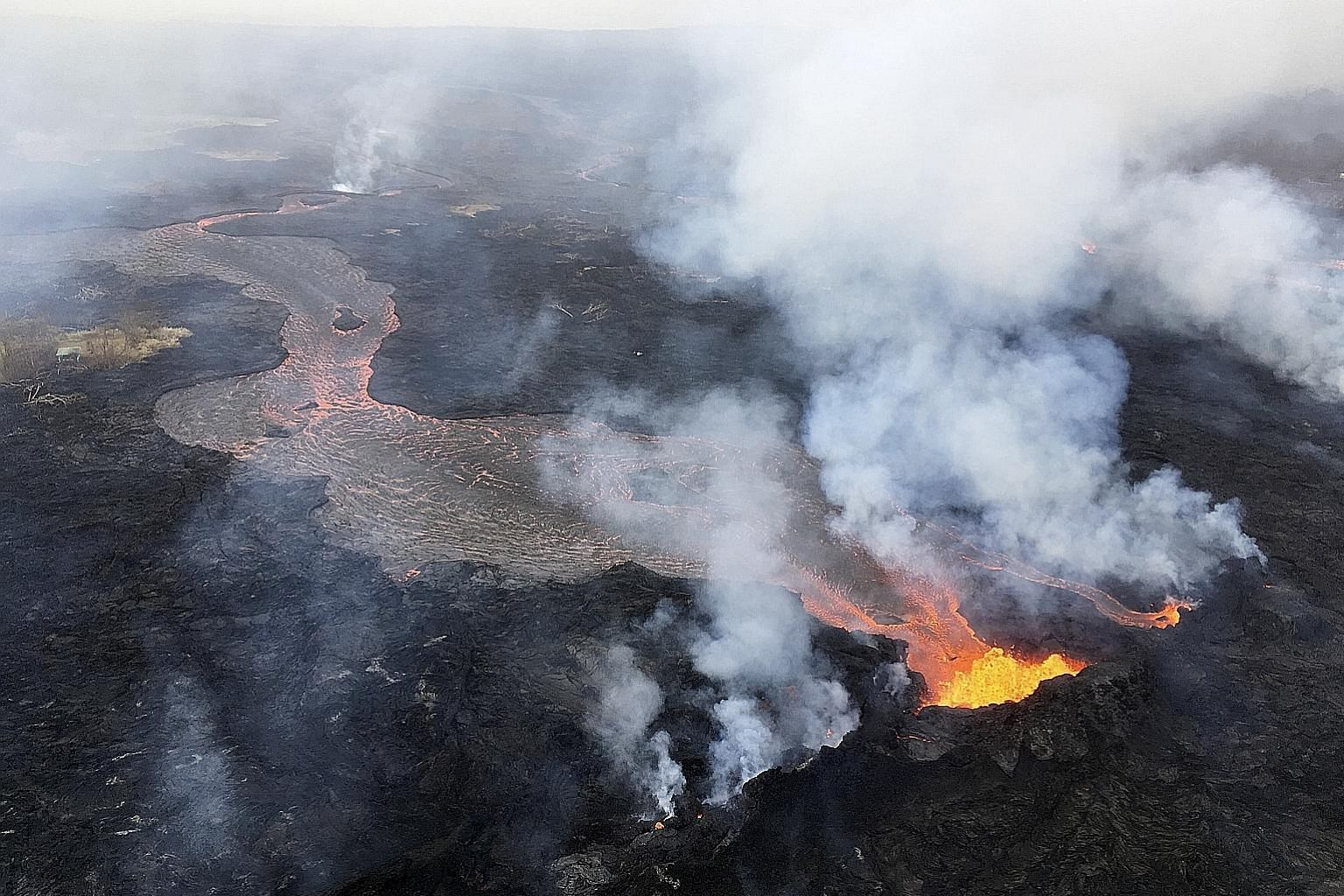 """Channellised lava flows from fissures on Kilauea in Hawaii spilling into the ocean on Thursday. Geologists said that after three weeks of escalating activity, Kilauea volcano has entered a """"steady state"""" of eruption."""