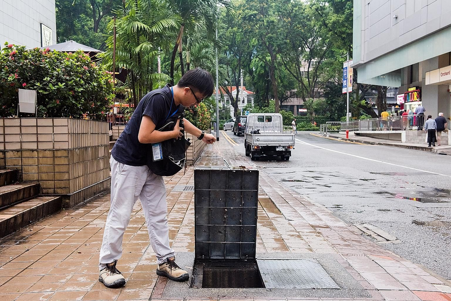 Above: Murky water flooding Cavenagh Road near Kramat Lane yesterday. Left: Heavy rain pelting down in the afternoon in Chinatown. Contractor Toh Wei Kian checking the drains in the Orchard Road area to see if any needed repair.