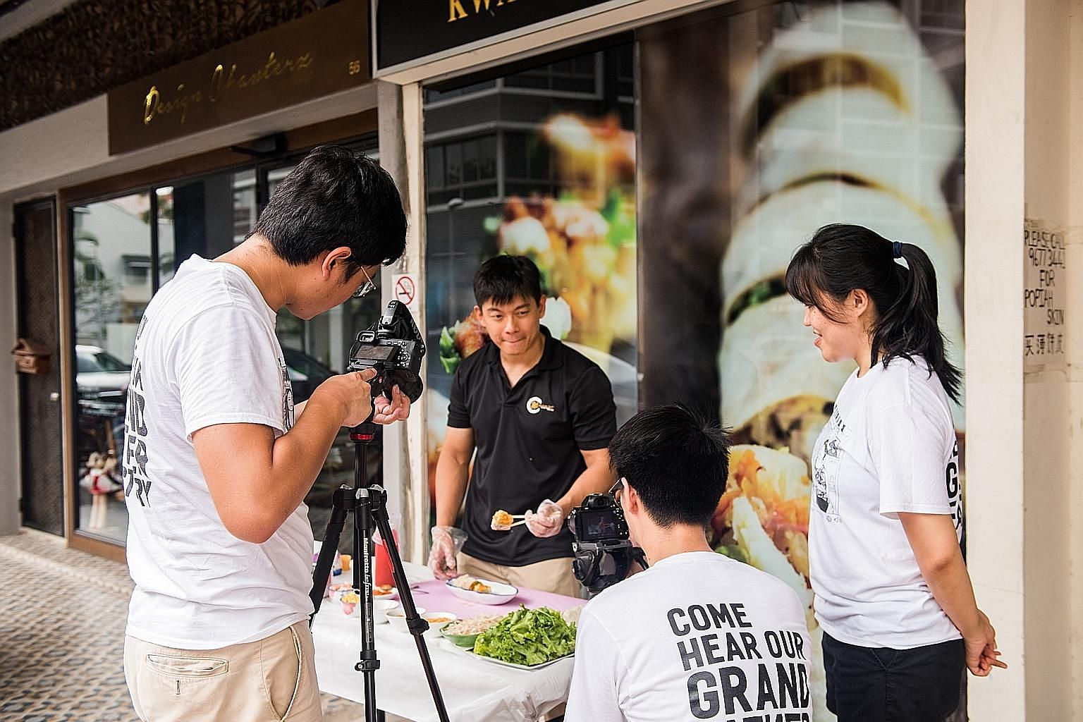 Our Grandfather Story team with (foreground, from left) Mr Ng Kai Yuan, Mr Matthew Chew and Ms Carine Tan, filming a clip. Their first video, which featured pink and green ice-cream bread from Jackson Bakery & Confectionery in Bedok, had over 150,000