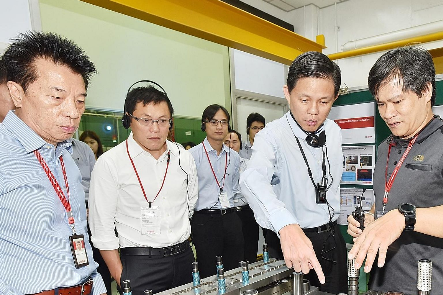 Minister of Trade and Industry Chan Chun Sing (second from right) during a visit to Molex Singapore's factory yesterday to view its automation and upskilling efforts.