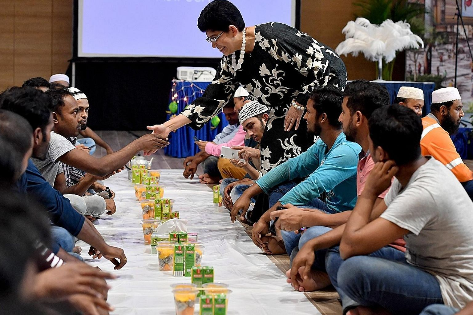 MP for Marine Parade GRC Fatimah Lateef shaking hands with a migrant worker during the Ramadan break fast session for about 240 migrant workers at Wisma Geylang Serai yesterday.