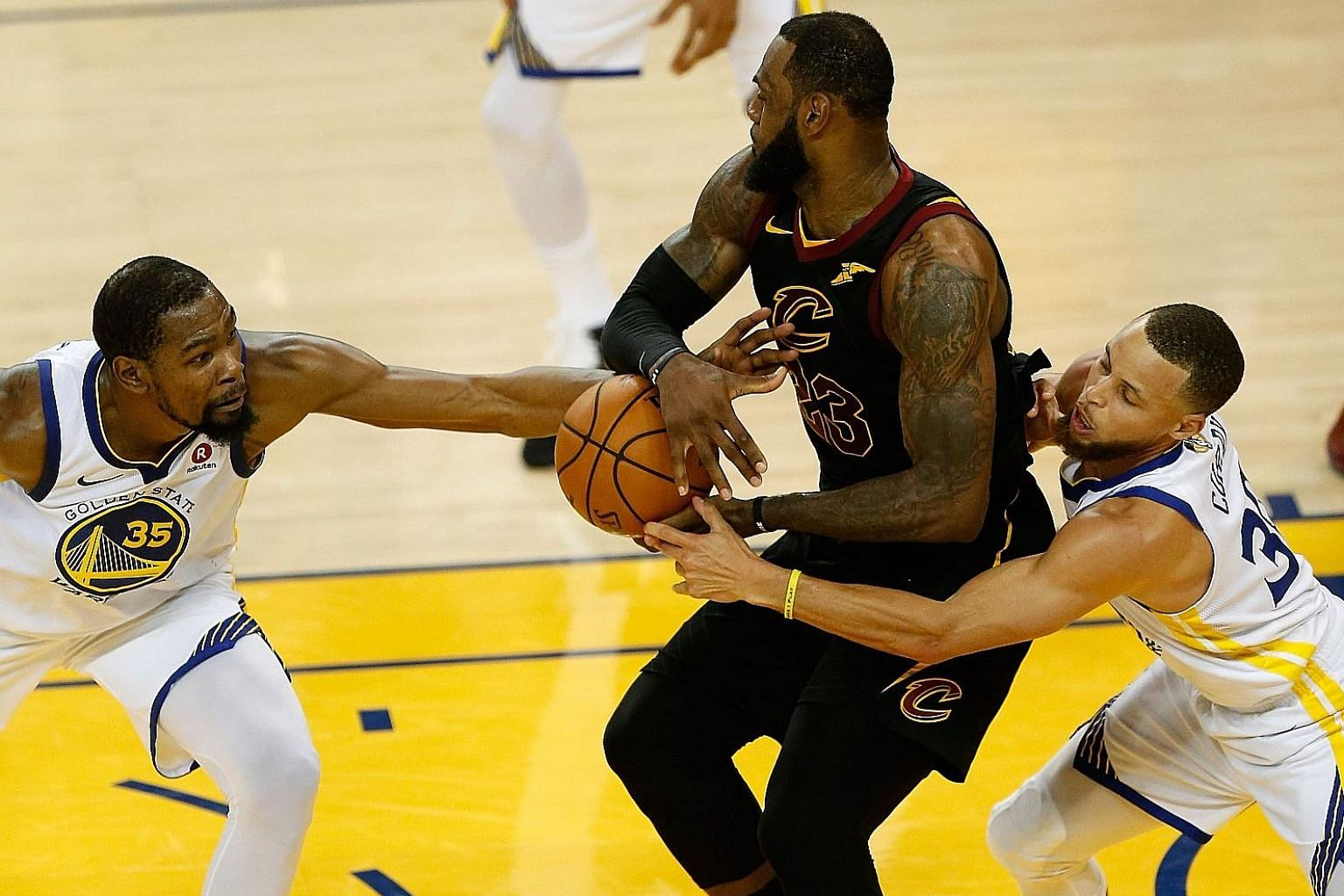 LeBron James of the Cleveland Cavaliers is defended by Kevin Durant (left) and Stephen Curry of the Golden State Warriors in Game 1 of the NBA Finals yesterday. The Warriors won 124-114 in overtime after the scores were tied 107-107 in regulation. Ja