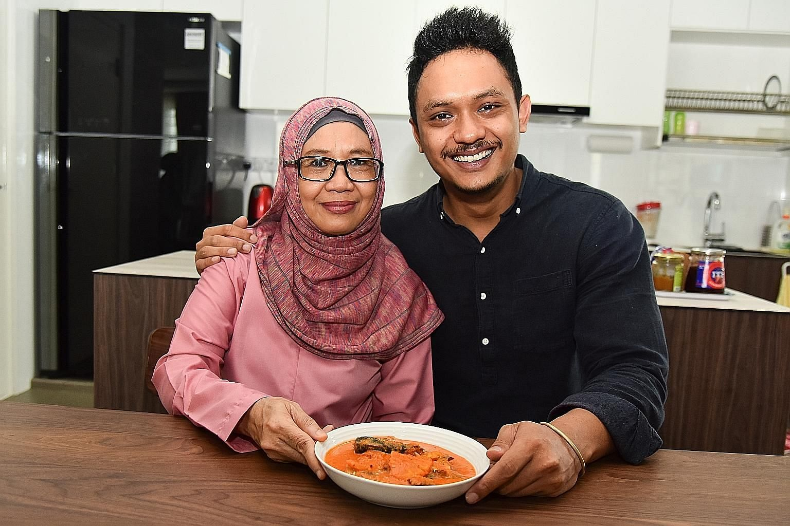 Ms Sohanah Mohamed Eusoff with her son Muhammad Sharizzat and his favourite dish, her sardines and pineapple in tangy and spicy coconut sauce.