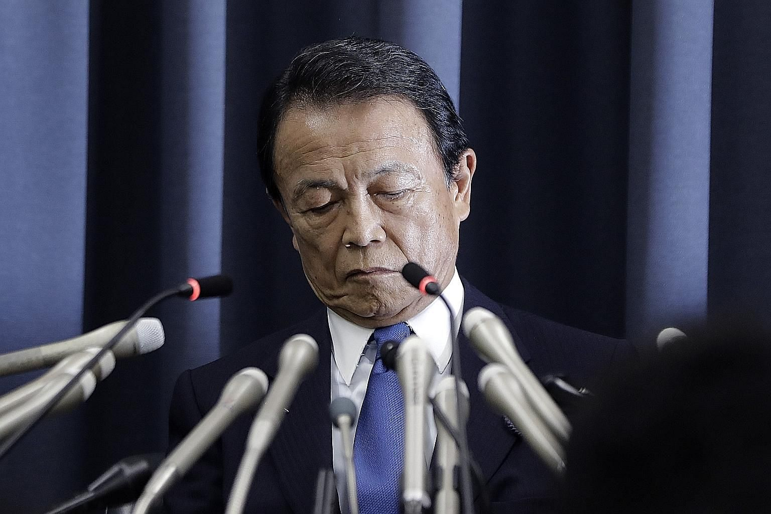 Japanese Finance Minister Taro Aso at a news conference in Tokyo yesterday. He said that in the light of an internal ministry probe, some 20 ministry officials will be punished with either a fine, suspension, pay cut or warning.