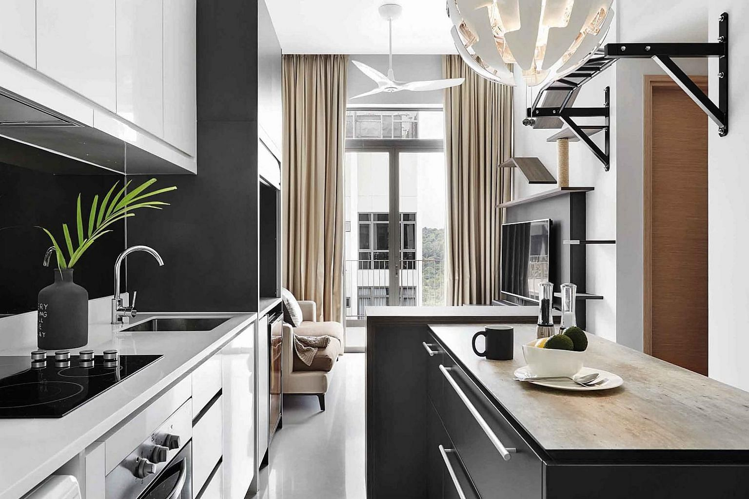 The space below the dining table conceals the food bowls and cat litter of the owner's pets, hence keeping the area visually clutter-free. A modern contemporary vibe permeates the apartment (left). The space below the loft (above) is an ideal spot fo