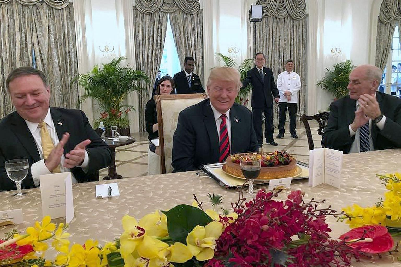 US President Donald Trump, who turns 72 on Thursday, celebrating his birthday early with Secretary of State Mike Pompeo (left) and Chief of Staff John Kelly yesterday. He was greeted with a birthday cake when he met Prime Minister Lee Hsien Loong for