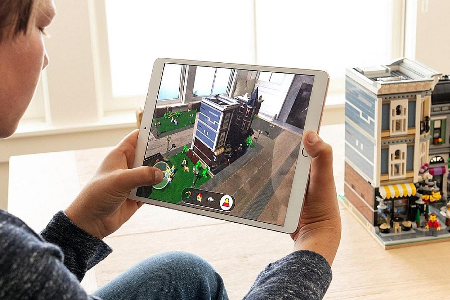 The Lego AR game (above) lets players add a virtual game world to a Lego building, then insert characters and vehicles. Memoji (left) lets users create customised animated emojis.