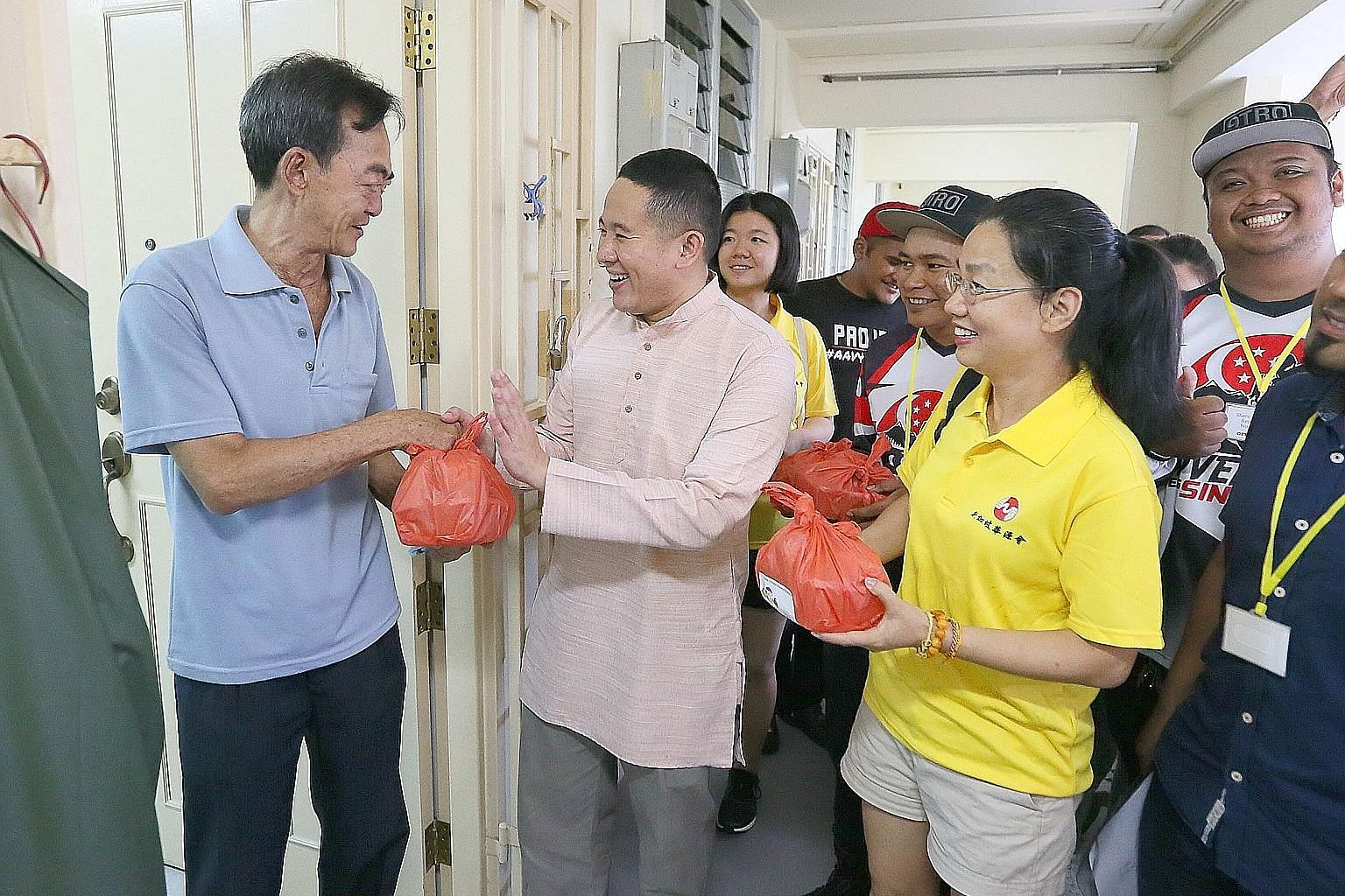 Senior Parliamentary Secretary and Sembawang GRC grassroots adviser Amrin Amin handing food to rental flat resident Lee Zhi Xin, 64. With him are Ms Wang Yi (right) and her daughter Zhao Jiayi. Over 100 volunteers packed food which was then delivered