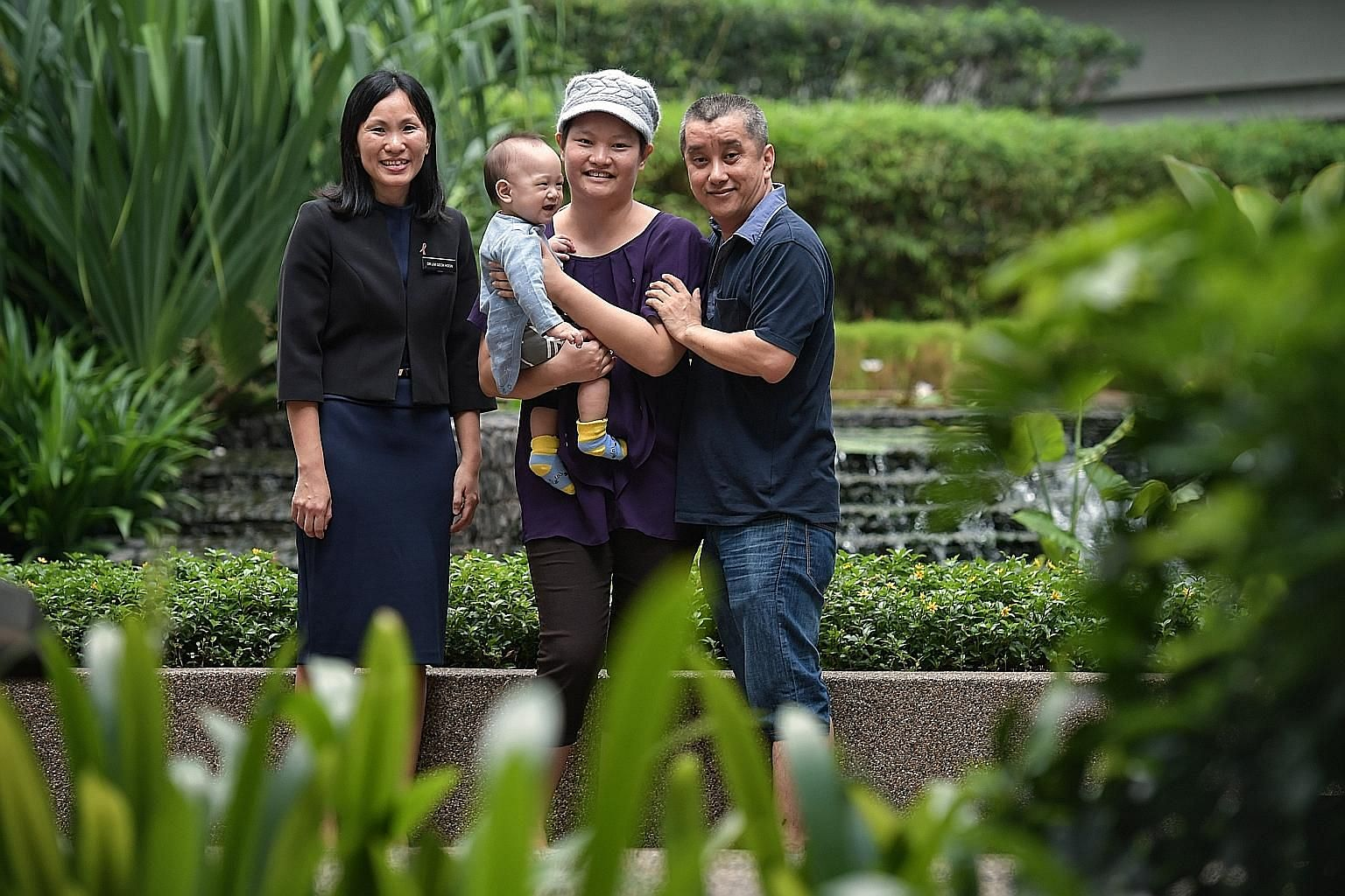 Madam May Wong carrying her 10-month-old son Tok Yuan Yi, with husband Sam Tok Hoe Tooi, 46, and Dr Lim Geok Hoon. Madam Wong underwent the minimal-scar mastectomy 10 days after giving birth to Yuan Yi.