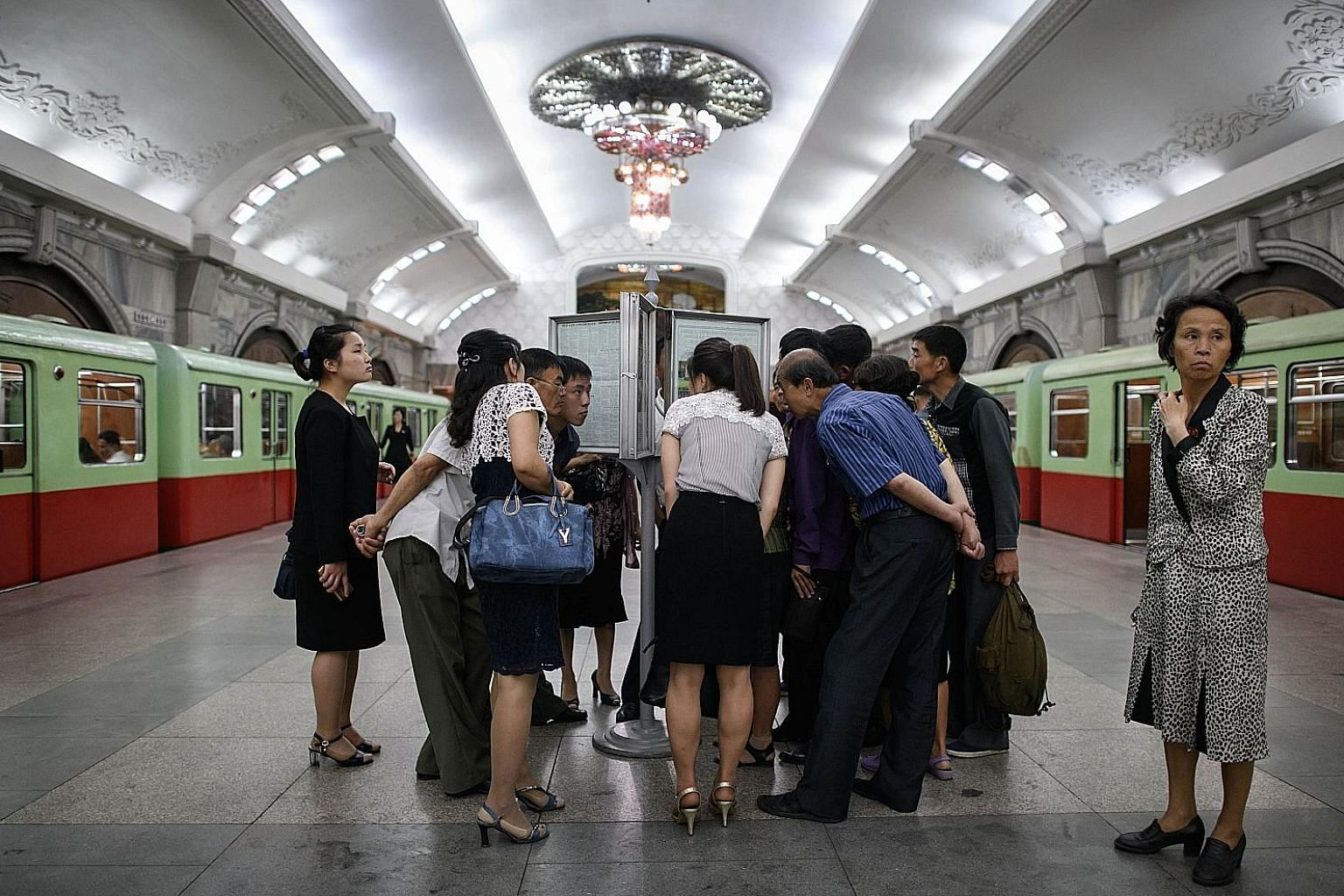 Commuters on a subway platform in Pyongyang, North Korea, reading yesterday's edition of the Rodong Sinmun newspaper, which featured images of North Korean leader Kim Jong Un meeting US President Donald Trump at their summit in Singapore on Tuesday.