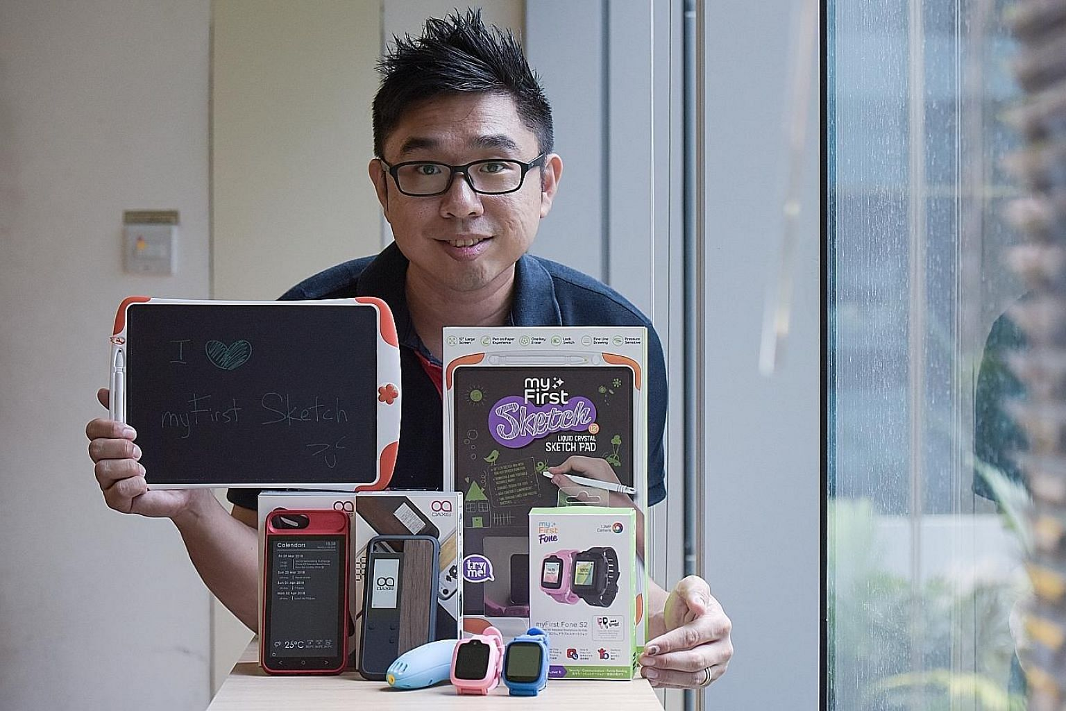 Oaxis chief executive and co-founder G-Jay Yong with the company's range of products, which include the WatchPhone S1 and its follow-up myFirst Fone S2 for children, as well as an E Ink screen for hospitals that displays queue numbers and patients' b