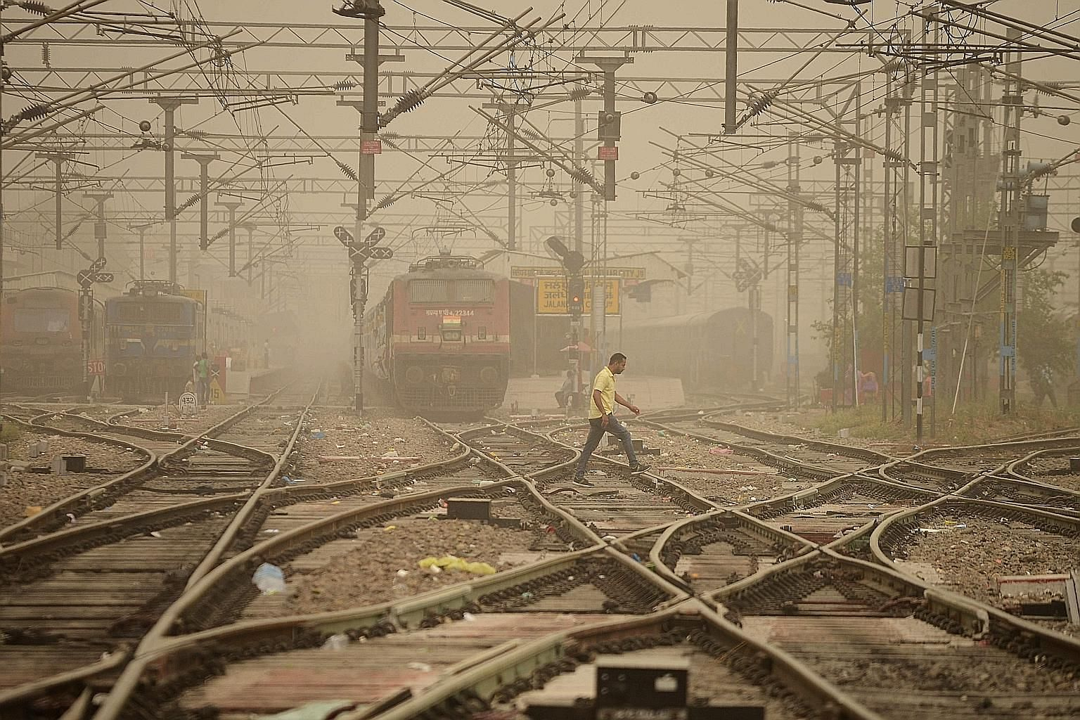 A railway crossing in Jalandhar, India, shrouded in dust yesterday. Meteorologists said dust storms in nearby desert areas had brought dust particles into Delhi. Combined with the existing pollutants in the air, this has resulted in smog-like conditi