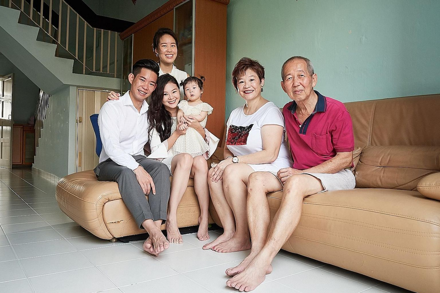 Mr Kenny Neo lives with (from left) his wife Vivian Chua, 26, one-year-old daughter Hailey, mother Poh Soo Fay, 58, father Jeffrey Neo, 66, and sister Debbie Neo, 28, (standing) in his parents' Housing Board maisonette near Heartland Mall in Kovan.