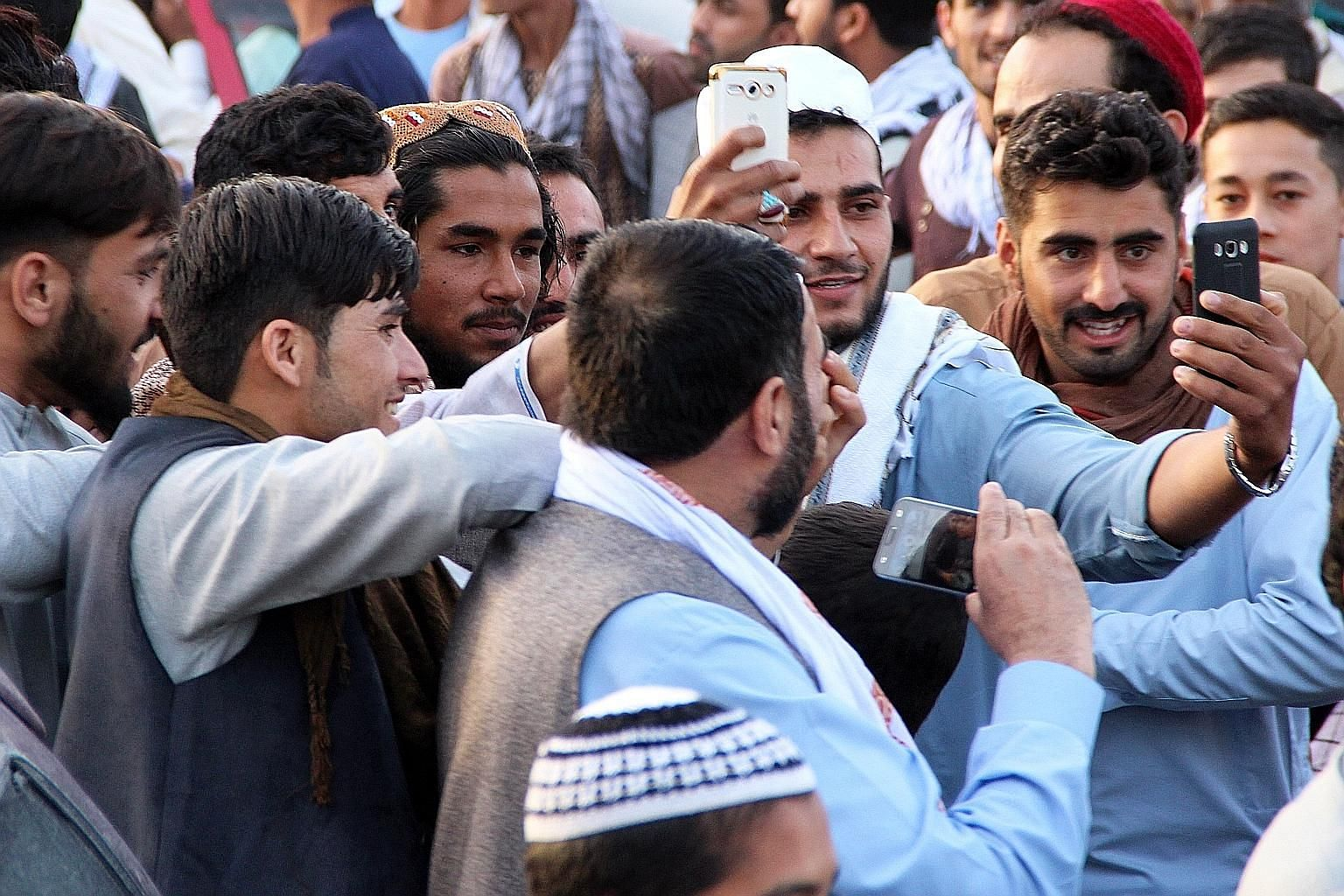 Afghans taking a selfie with a Taleban militant in Kunduz on Friday as the militants announced a three-day ceasefire over the Eid holiday in various parts of Afghanistan.