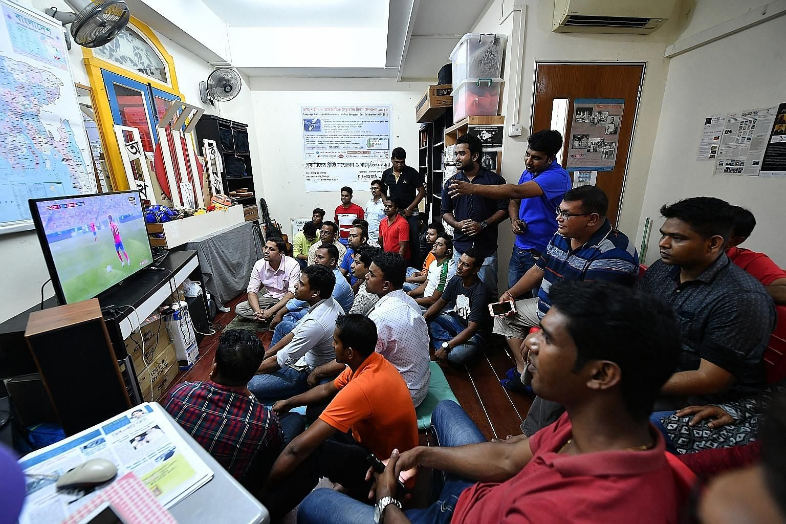 Foreign workers gathering at arts space Dibashram to catch the Costa Rica v Serbia match last night. The venue was provided by owner A.K.M. Mohsin, a Bangladeshi permanent resident. Muslim workers began their Hari Raya celebrations by going to the mo