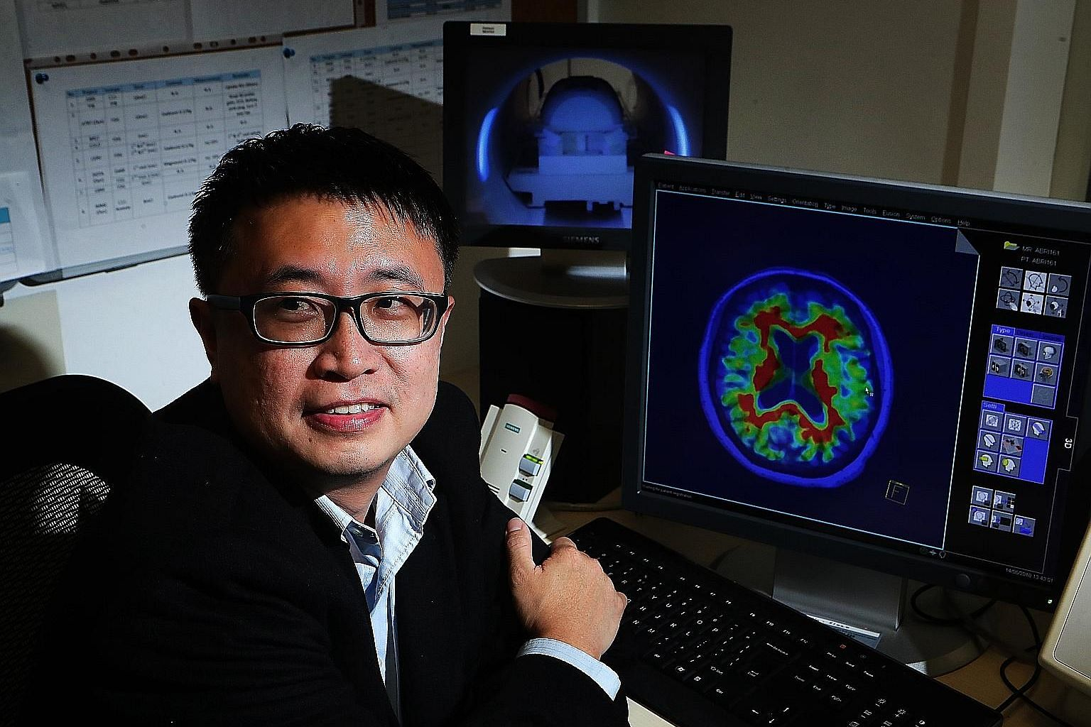 Assistant Professor Thomas Yeo with a magnetic resonance imaging scan of a human brain. The machine can be used to detect tumours or dementia. His main research interests include finding out how different people are vulnerable to mental disorders.