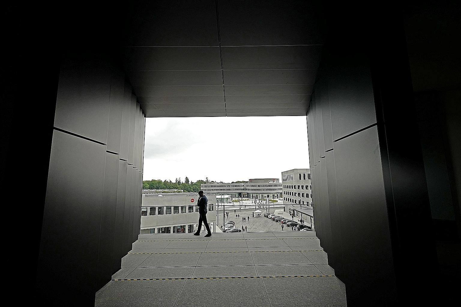 """A view from inside the giant """"viewfinder"""" balcony of the new Leica Camera AG building that gives visitors a bird's eye view of the Leitz Park complex. Leica Archive guide Maria-Victoria Furst showing historical items such as shovels used for ground-b"""