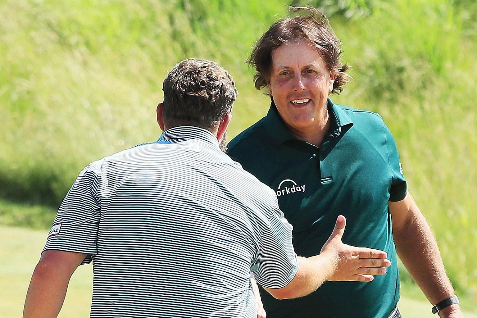 Andrew Johnston and Phil Mickelson shake hands on the 18th green during the third round of the US Open on Saturday. Johnston stopped short of condemning the American, who received a two-stroke penalty.