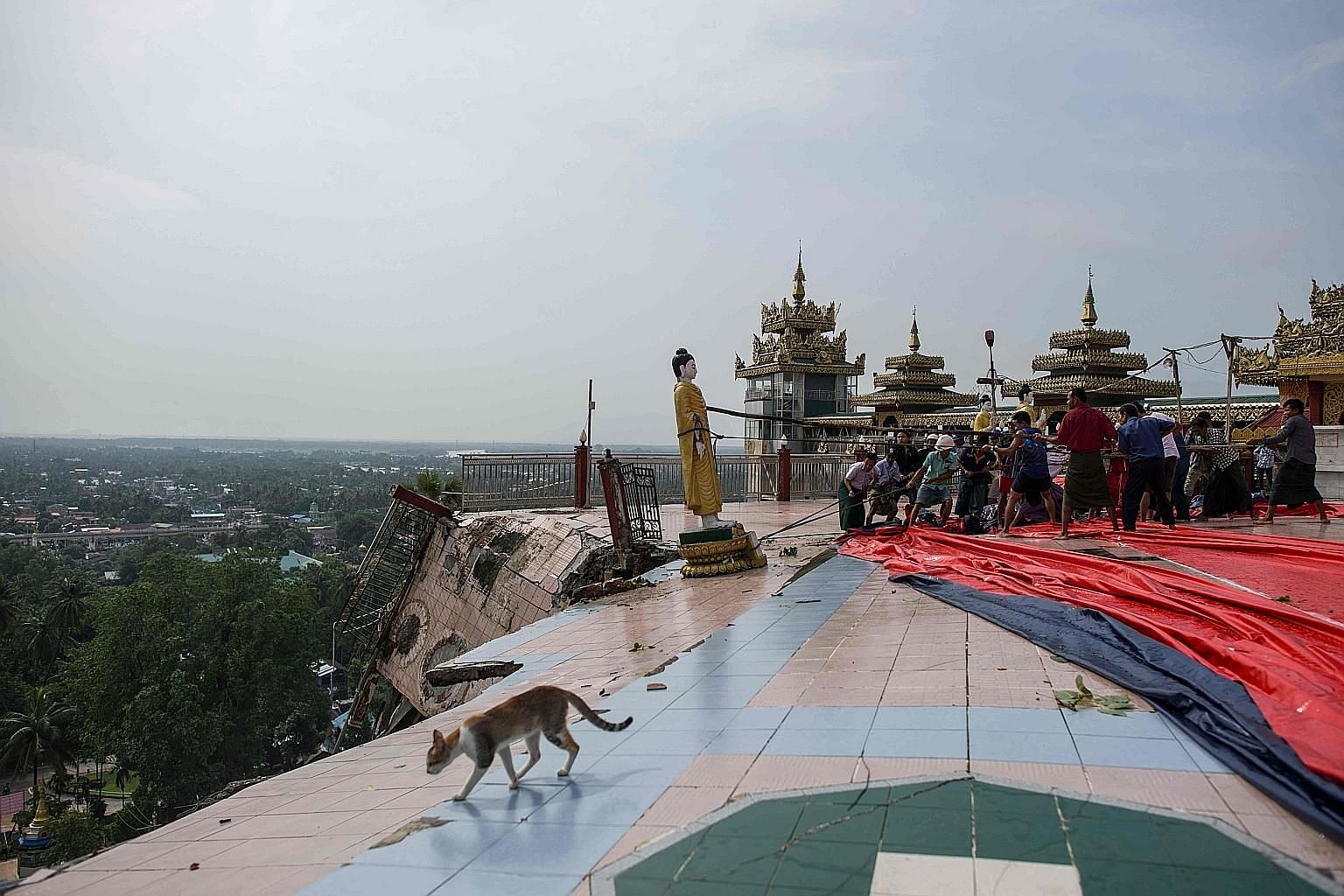 Workers trying to prevent a Buddha statue from slipping off a cliff after a landslide damaged the hilltop Kyeik Than Lan pagoda in Mawlamyine, in Myanmar's Mon state, yesterday.