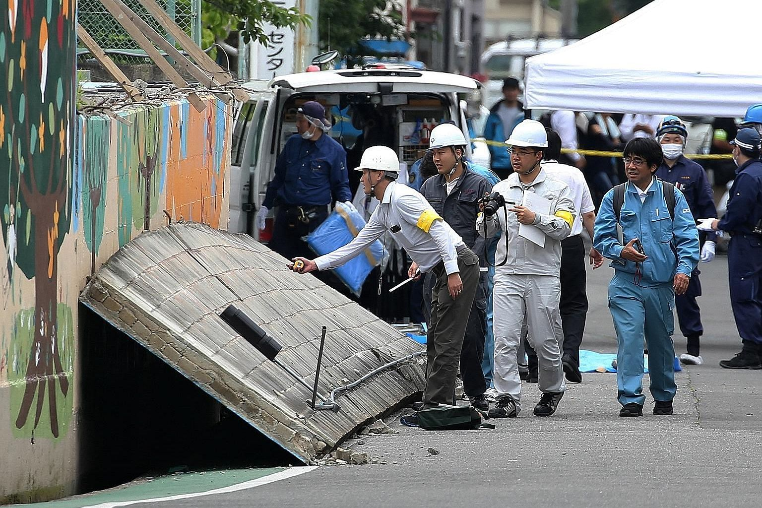 Investigators yesterday checking the collapsed wall that killed a nine-year-old girl at an elementary school in Takatsuki, Osaka prefecture. The education ministry said it would instruct education boards nationwide to inspect school buildings, after