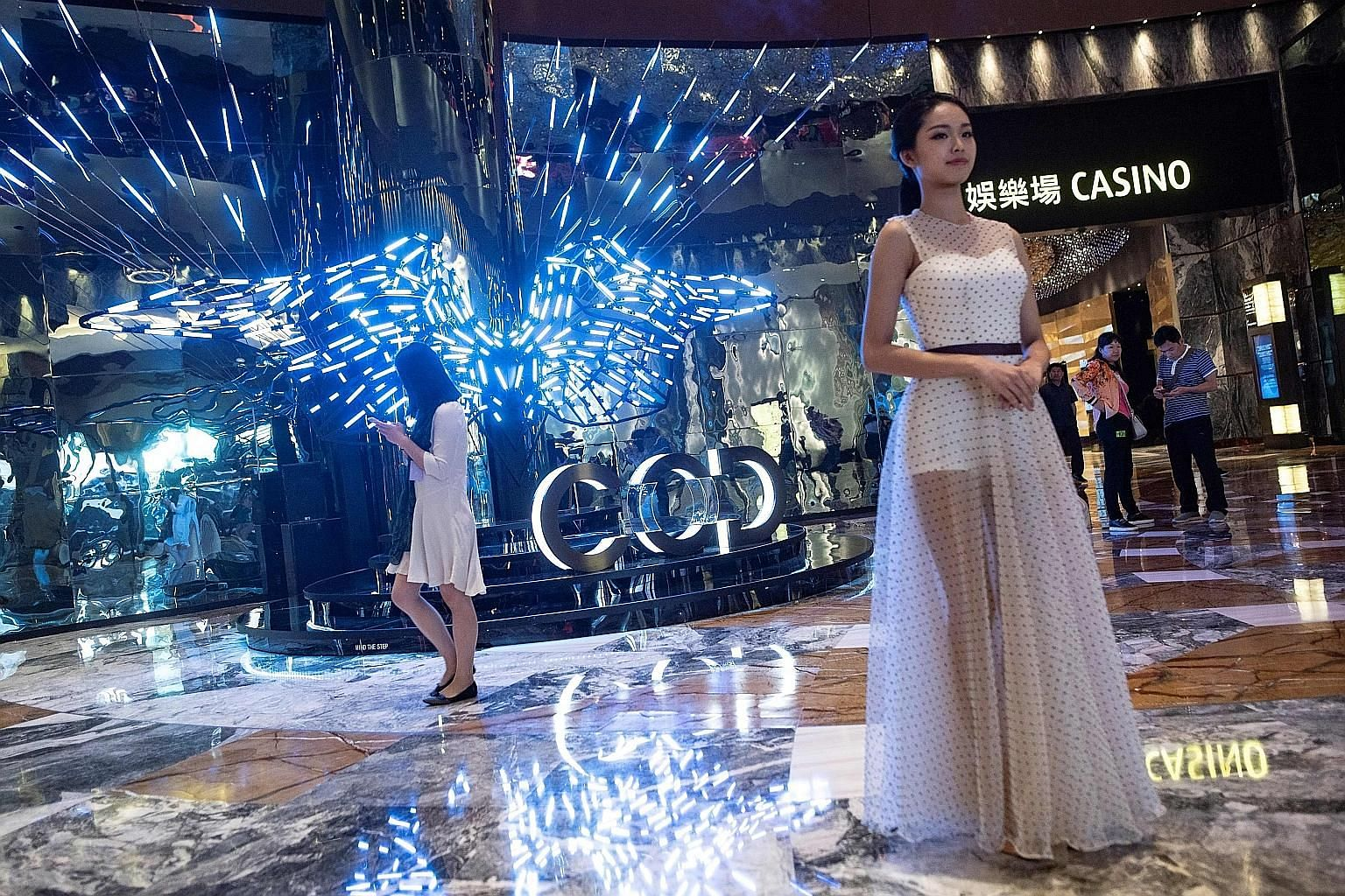 A receptionist standing ready last Friday to greet visitors to the casino section of Morpheus resort's City of Dreams in Macau. The hotel, owned by Melco Resorts & Entertainment, opened last week.