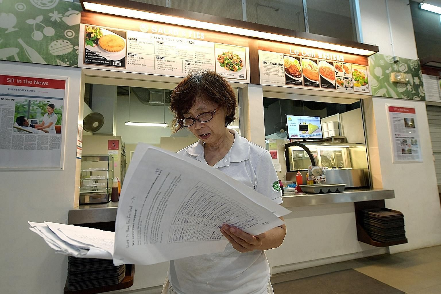 Madam Ong Swee Geok, who runs a salad stall, holding the petition signed by students, staff and other vendors protesting against the rising costs. She was told last month by Food Canopy, which leases out SIT's cafeteria stall spaces, that she would h
