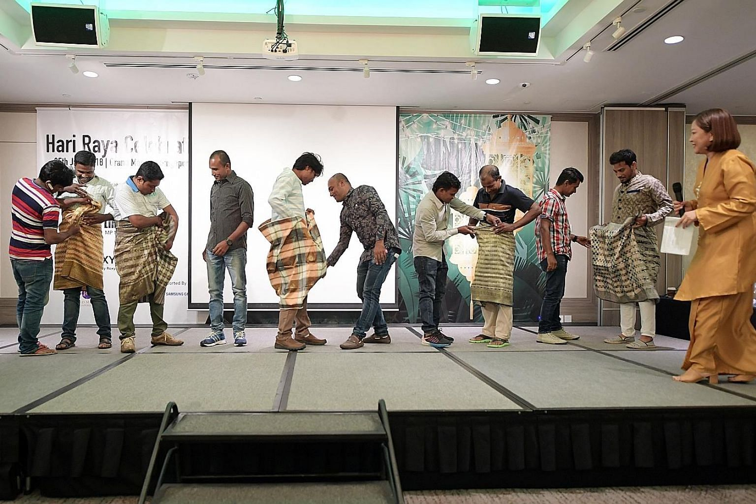 Foreign workers trying to knot a samping - a short version of a sarong - during a game at a dinner organised by Roxy Foundation and Samsung C&T Corporation last night. The dinner, held at Grand Mercure Singapore Roxy to mark Hari Raya Aidilfitri, was
