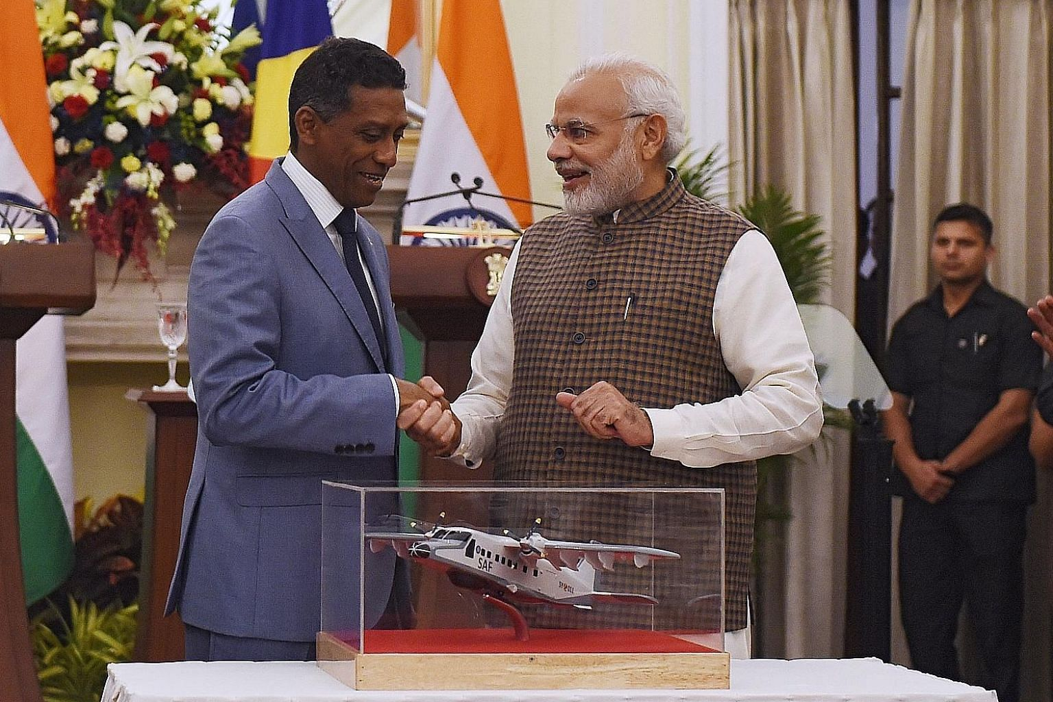 Seychelles President Danny Faure (left) and India's Prime Minister Narendra Modi with a model of a Dornier aircraft.