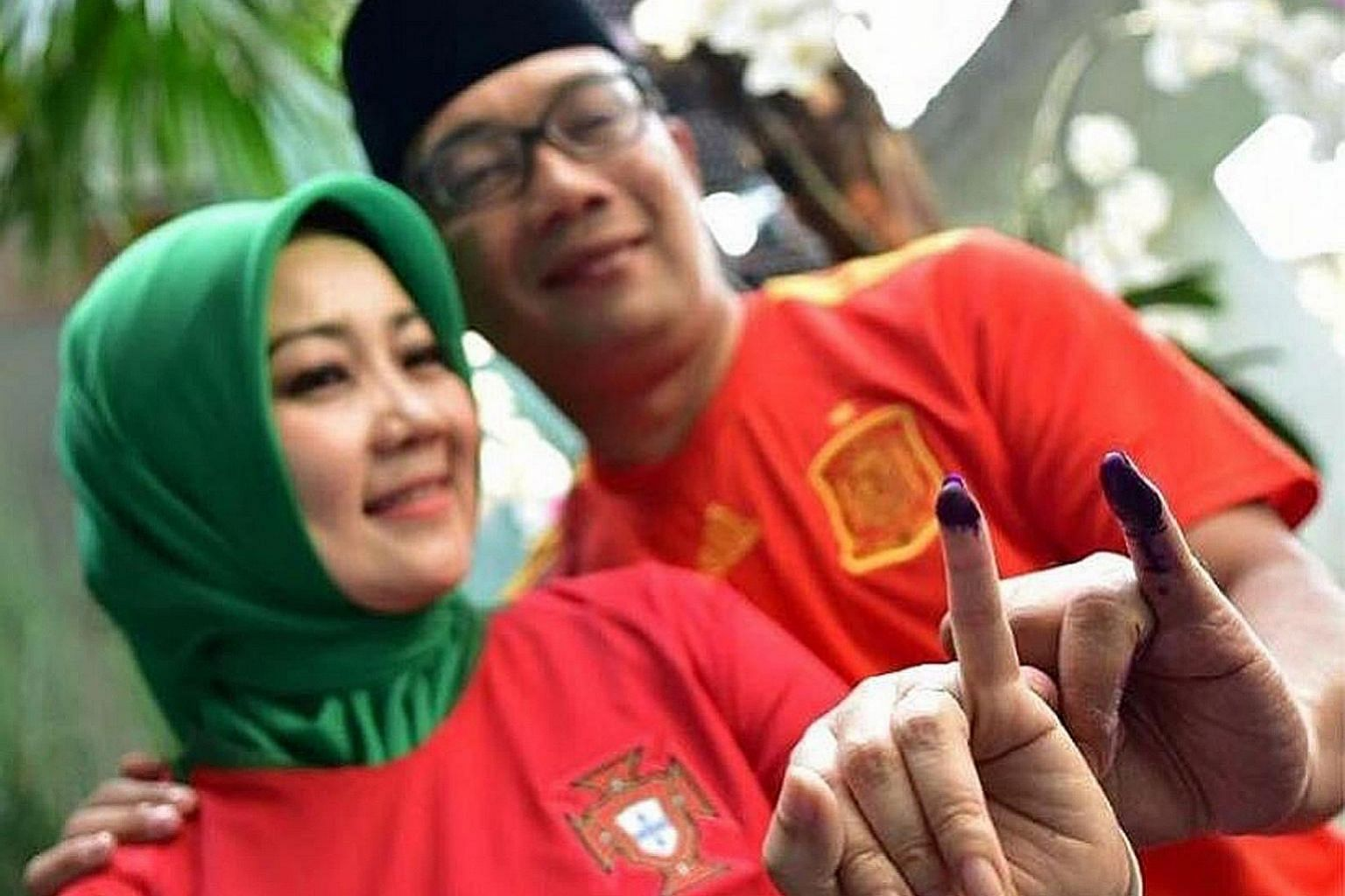 Bandung Mayor Ridwan Kamil and his wife Atalia Praratya showing their marked fingers after voting yesterday.