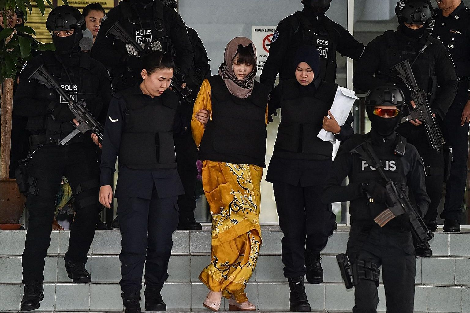 Vietnamese suspect Doan Thi Huong being escorted by Malaysian police after a court session for her trial at the Shah Alam High Court in Shah Alam, outside Kuala Lumpur, yesterday. She was allegedly involved in the assassination of Mr Kim Jong Nam, th