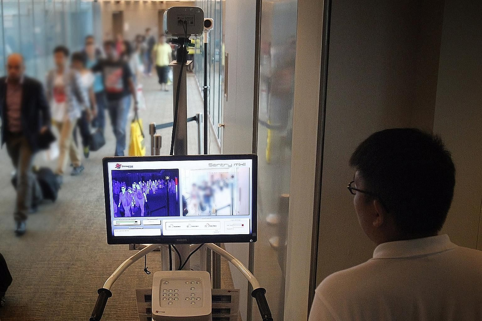 Passengers arriving at Changi Airport walking past a thermal scanner when temperature screening was on for the Middle East respiratory syndrome (Mers) in 2014. With inexpensive travel and increased connectivity, pathogens cross borders with alarming