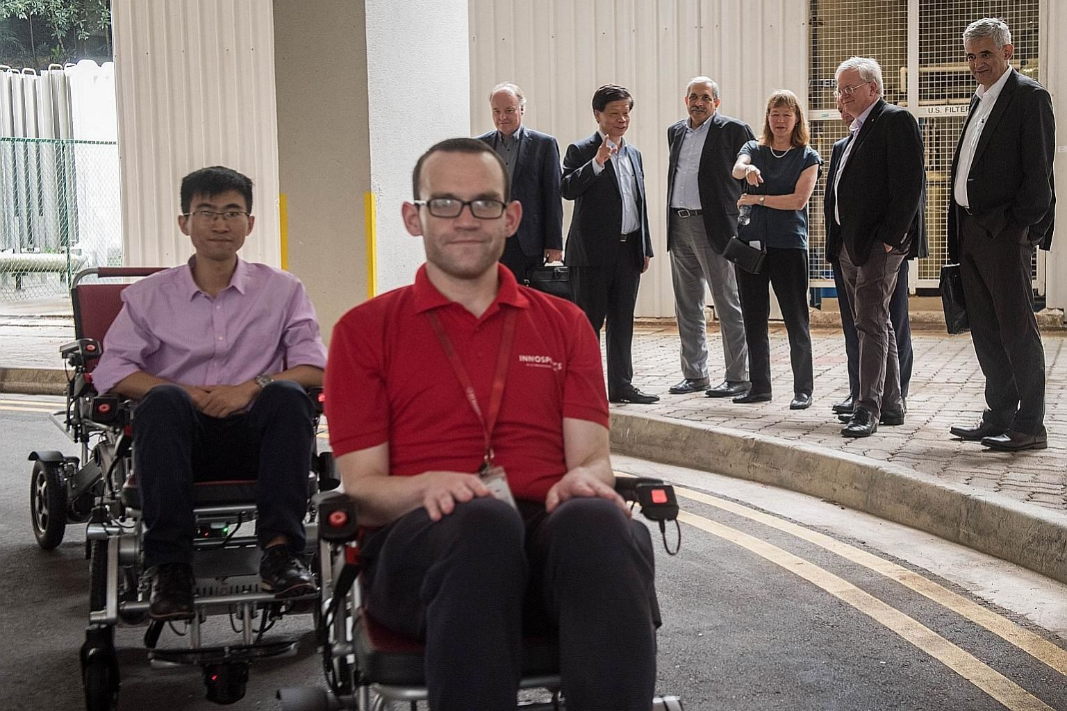 Members of the International Academic Advisory Panel observing a demonstration of Folo Fleet, a semi-autonomous smart mobility device convoy system, at NTU on Wednesday, as part of their three-day meeting. Key topics discussed were the value of a deg