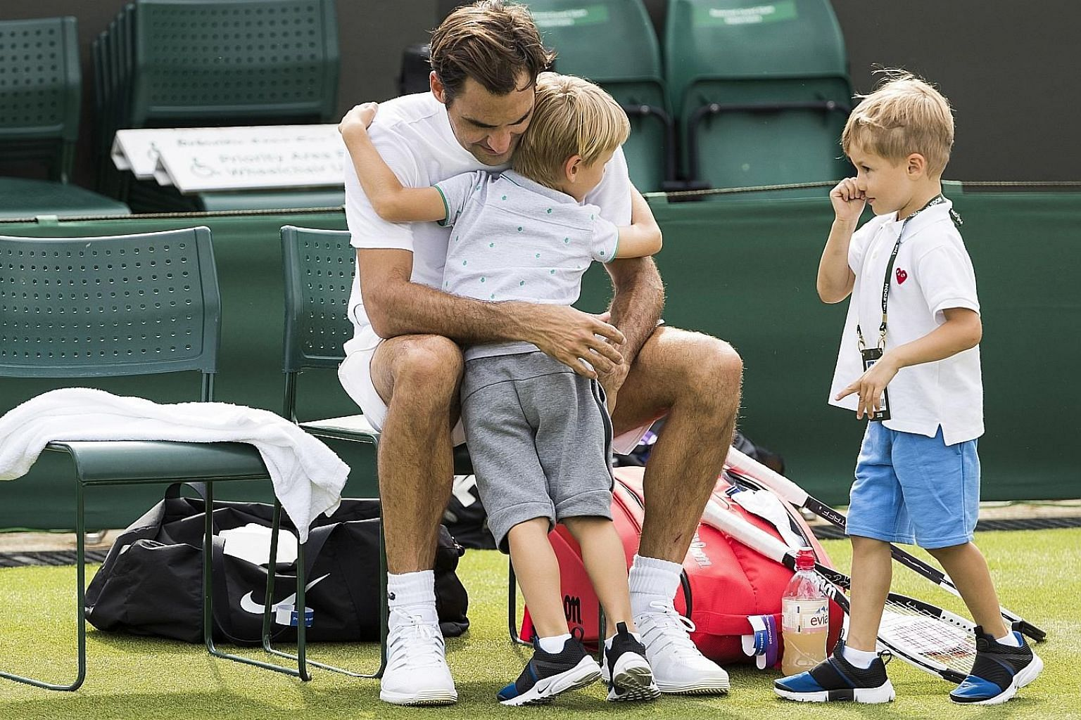 Roger Federer hugging his twin boys, Leo and Lenny, at the end of a training session in Wimbledon on Thursday. The defending champion opens his bid for a record ninth Wimbledon crown by facing Serbia's Dusan Lajovic on Monday.