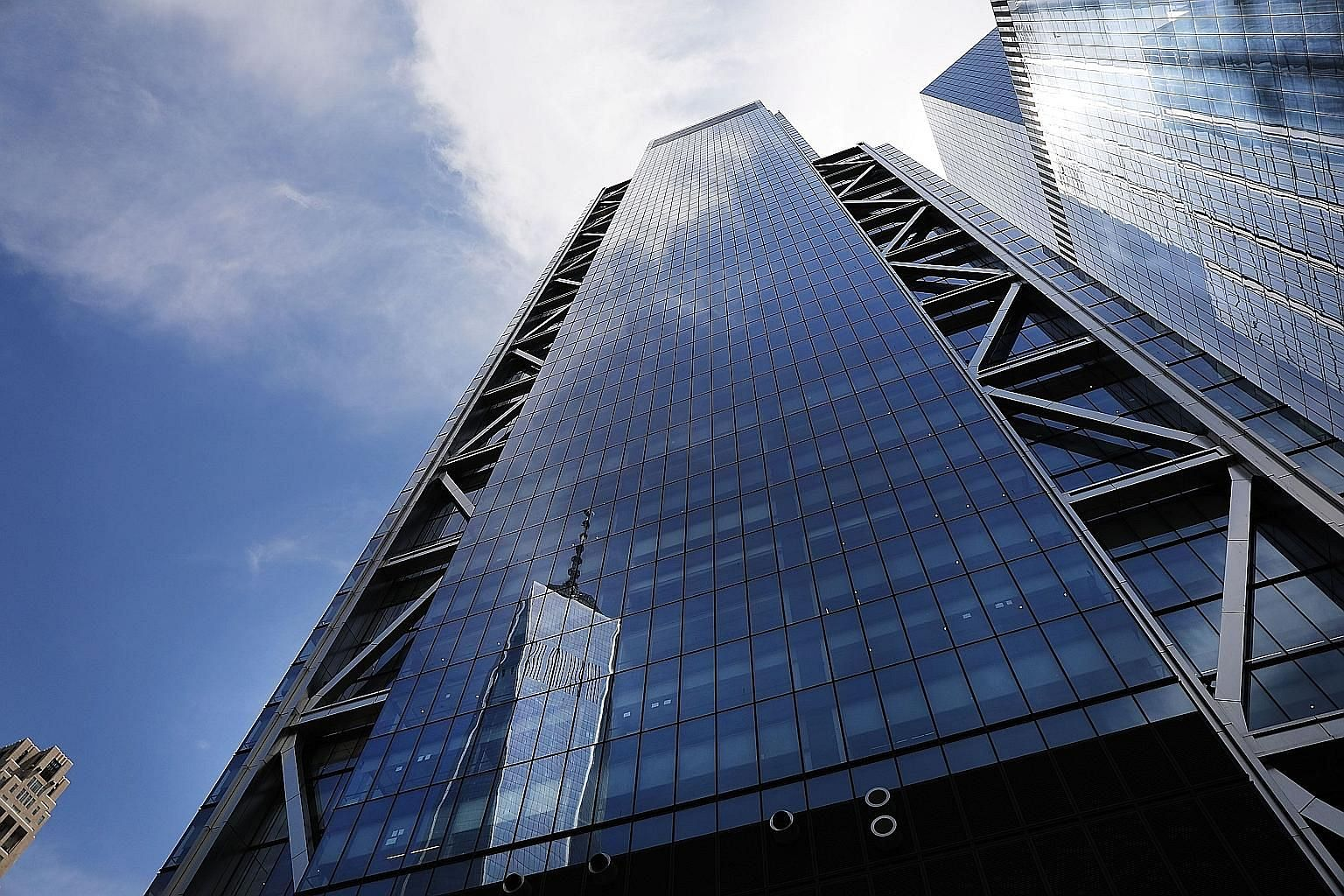 One World Trade Center is reflected in the glass windows of Three World Trade Center (above), a project of American property developer Larry Silverstein (left).
