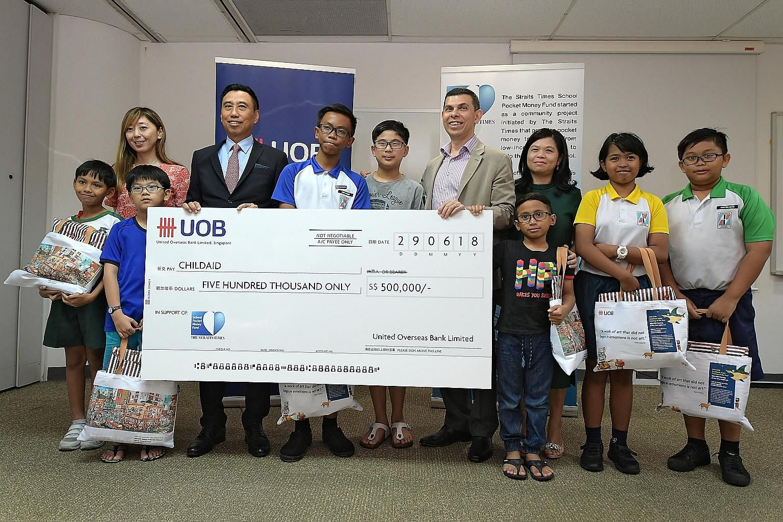 Seven beneficiaries of The Straits Times School Pocket Money Fund posed for a picture at yesterday's cheque presentation event with (from left) ST executive editor Sumiko Tan, Mr Eric Tham, Mr Warren Fernandez and STSPMF general manager Tan Bee Heong